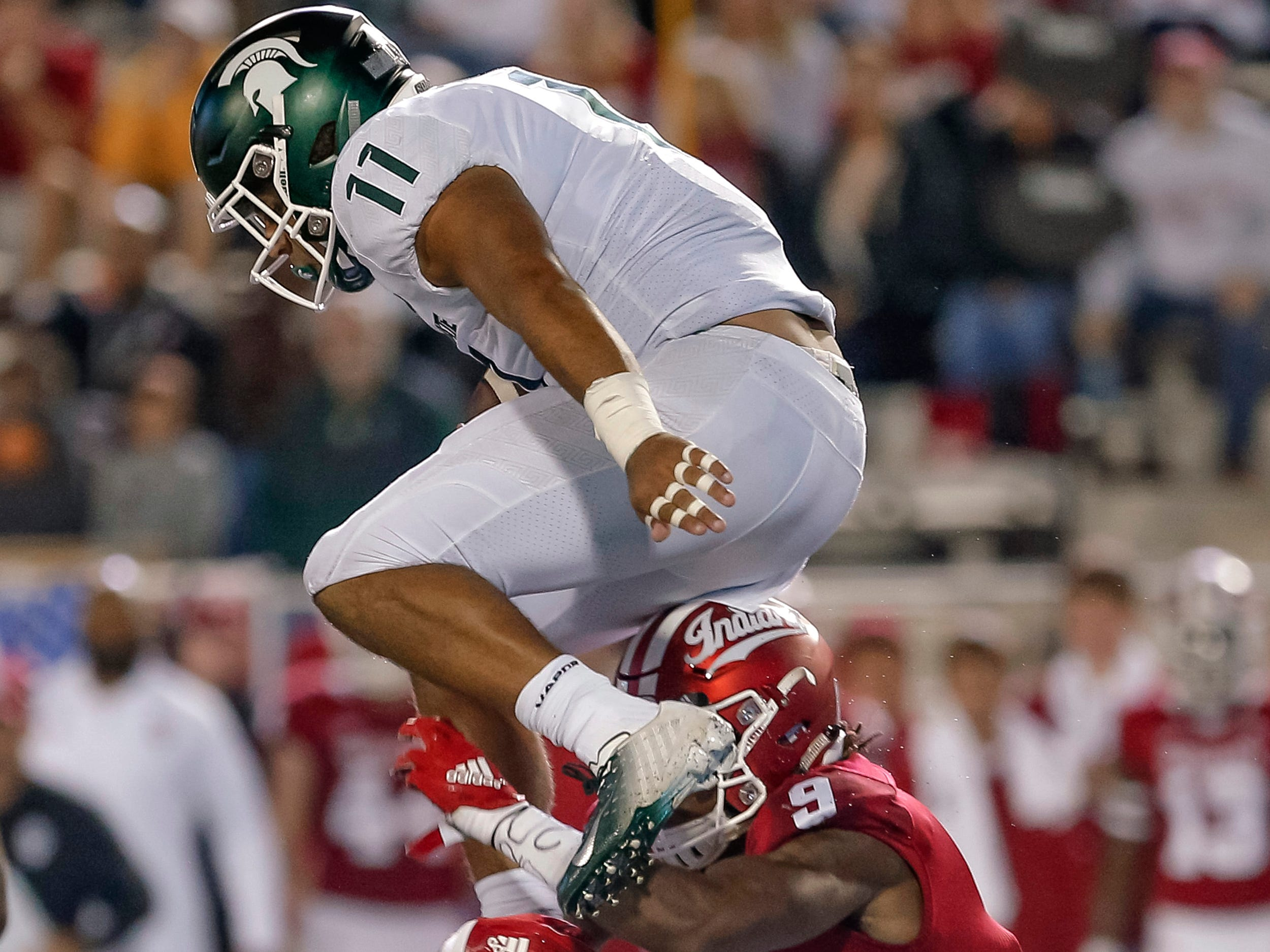 Connor Heyward #11 of the Michigan State Spartans leaps over Jonathan Crawford #9 of the Indiana Hoosiers during the second half of the game at Memorial Stadium on September 22, 2018 in Bloomington, Indiana.