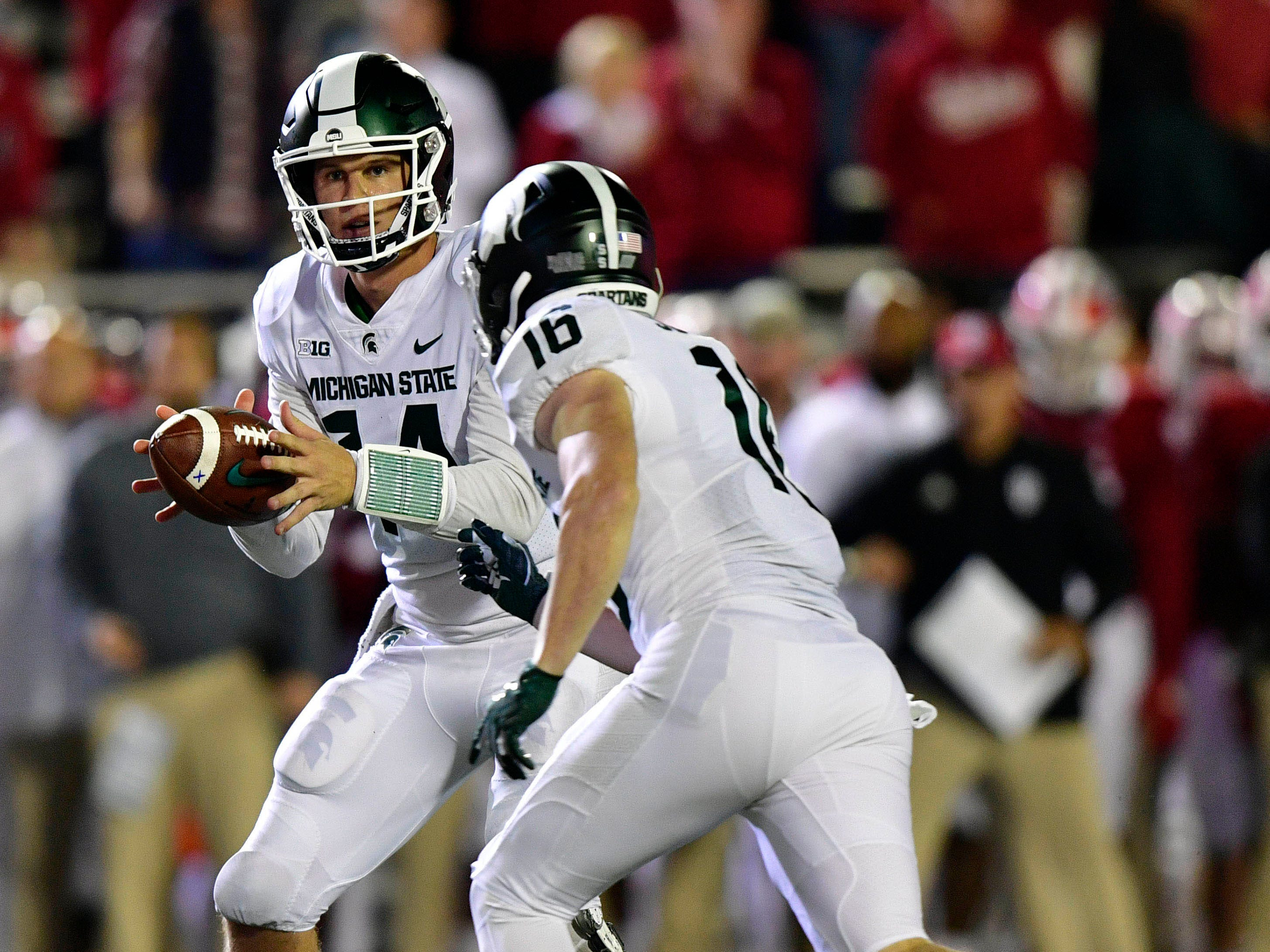 Michigan State Spartans quarterback Brian Lewerke (14) pitches a ball to  Spartans wide receiver Brandon Sowards (16) during the second half of the game against Indiana at Memorial Stadium. The Michigan State Spartans defeated the Indiana Hoosiers 35 to 21.