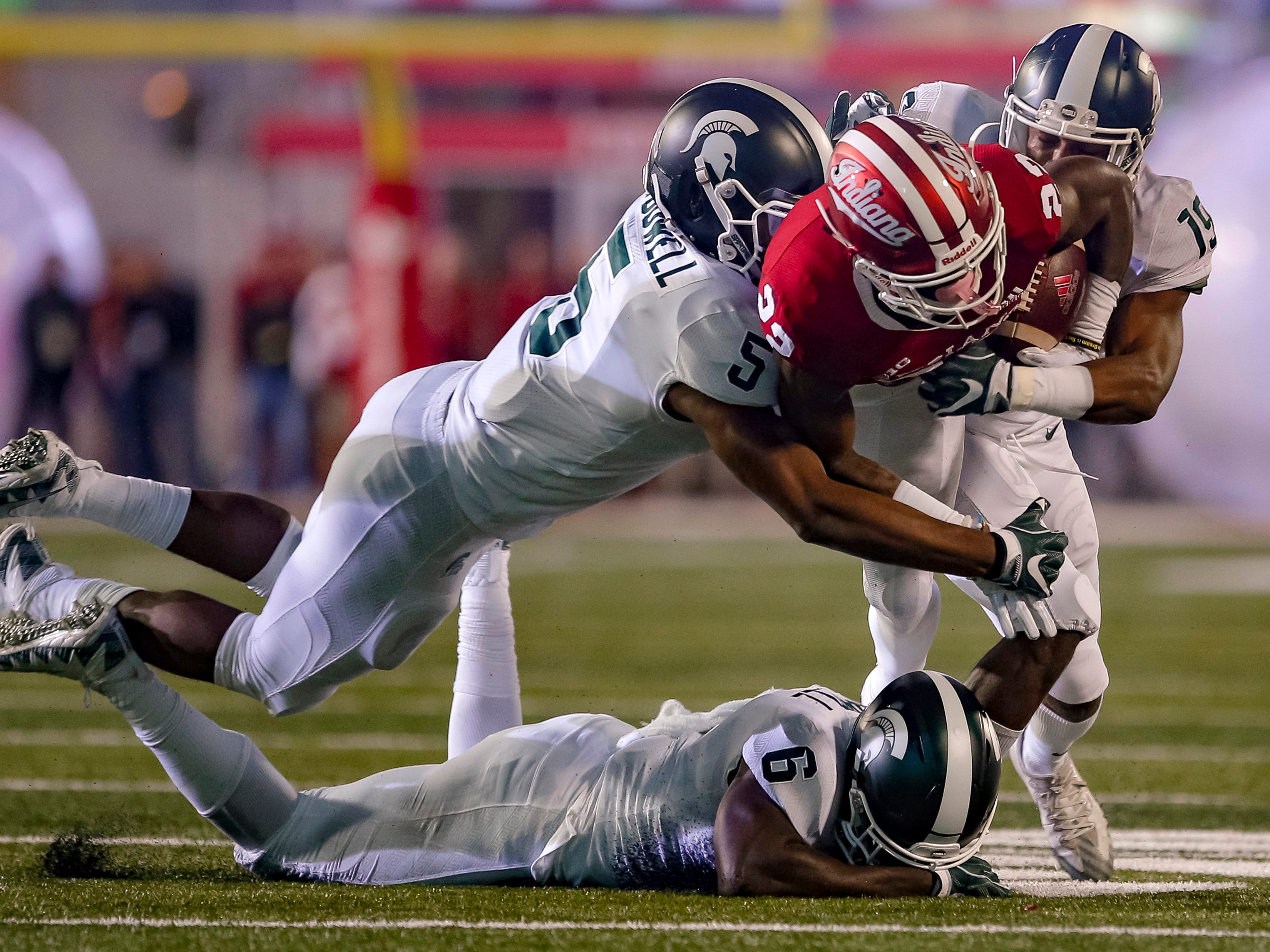 Whop Philyor #22 of the Indiana Hoosiers is tackled while rushing by Andrew Dowell #5 and Josh Butler #19 of the Michigan State Spartans during the game at Memorial Stadium on September 22, 2018 in Bloomington, Indiana.