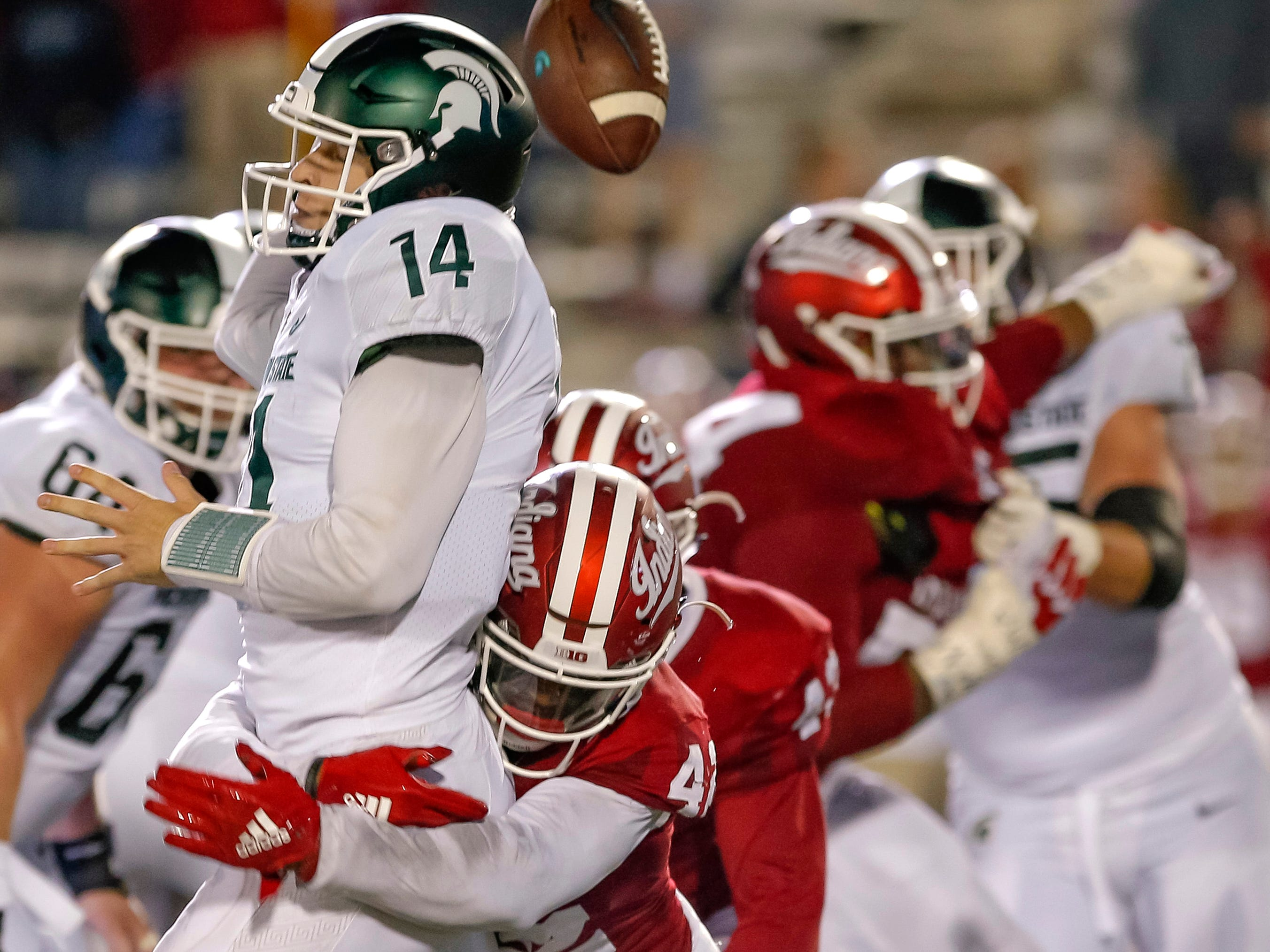 Brian Lewerke #14 of the Michigan State Spartans fumbles the ball while throwing as Marcelino Ball #42 of the Indiana Hoosiers makes the hit at Memorial Stadium on September 22, 2018 in Bloomington, Indiana.