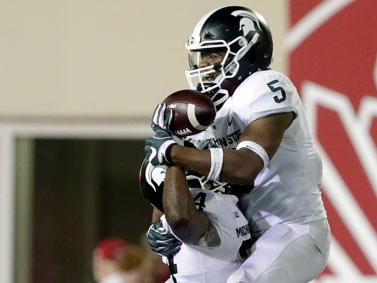 Michigan State's Antjuan Simmons (34) and Andrew Dowell celebrate after Simmons recovered a fumble during the second half of an NCAA college football game against Indiana, Saturday, Sept. 22, 2018, in Bloomington, Ind. Michigan State won 35-21.