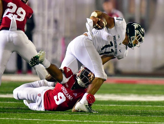 Michigan State Spartans running back Connor Heyward (11) is brought down by Indiana Hoosiers defensive back Jonathan Crawford (9) during the second half of the game at Memorial Stadium. The Michigan State Spartans defeated the Indiana Hoosiers 35-21.