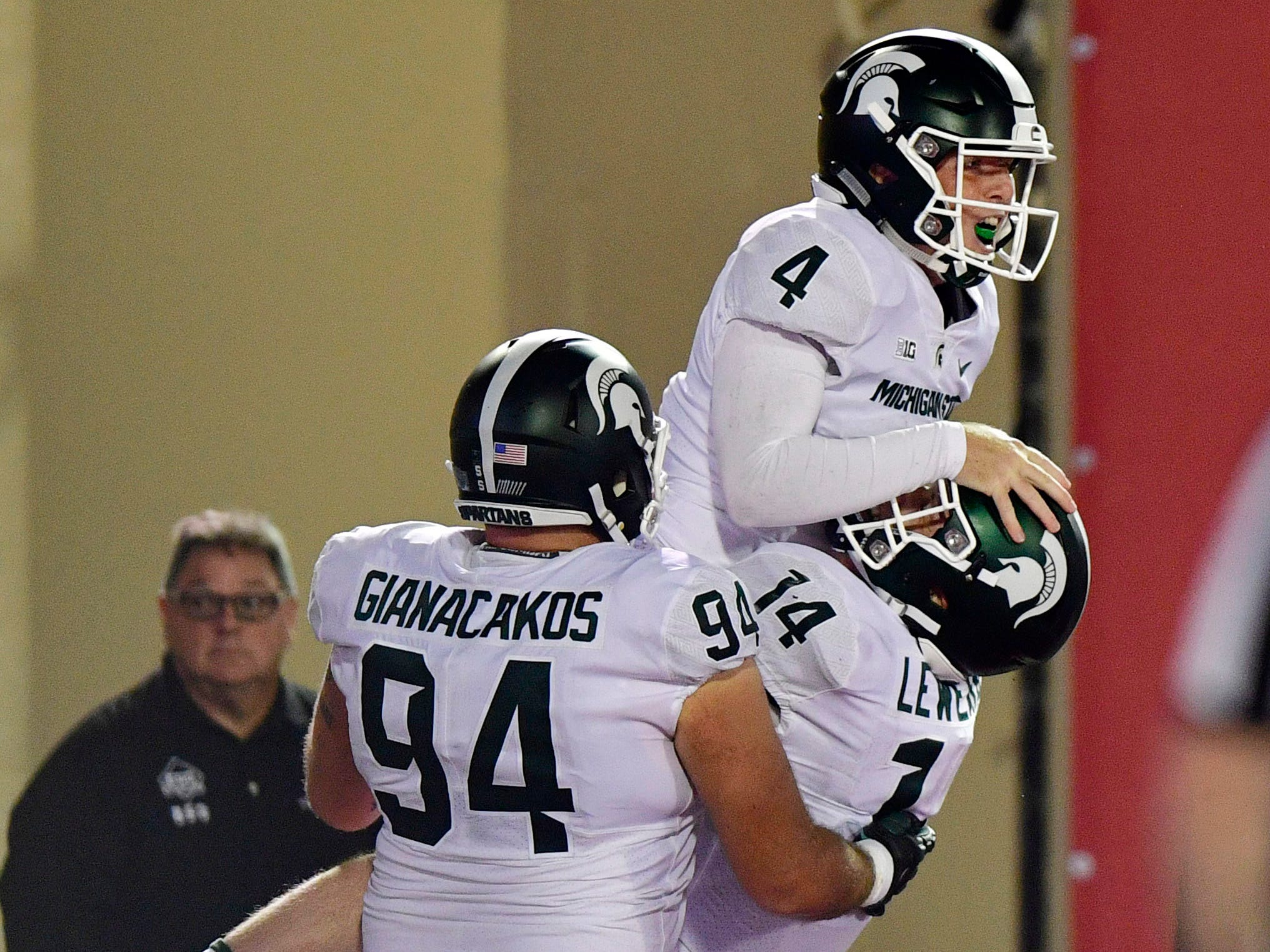 Michigan State Spartans wide receiver C.J. Hayes (4) jumps into the arms of quarterback Brian Lewerke (14) with tight end Chase Gianacakos (94) in celebration during the second half of the game against Indiana at Memorial Stadium. The Michigan State Spartans defeated the Indiana Hoosiers 35 to 21.