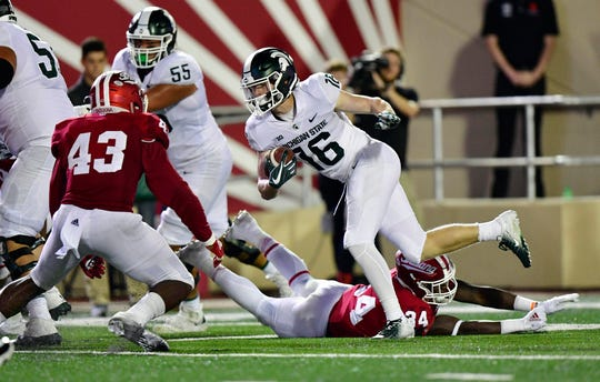 Michigan State Spartans wide receiver Brandon Sowards (16) dodges a tackle from Indiana Hoosiers linebacker Cam Jones (34) only to run into Hoosiers linebacker Dameon Willis Jr. (43) during the second half of the game at Memorial Stadium. The Michigan State Spartans defeated the Indiana Hoosiers 35 to 21.