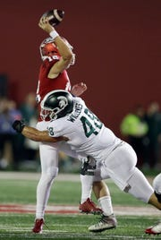 Indiana quarterback Peyton Ramsey throws an interception for a touchdown as he is hit by Michigan State's Kenny Willekes during the first half of an NCAA college football game, Saturday, Sept. 22, 2018, in Bloomington, Ind.