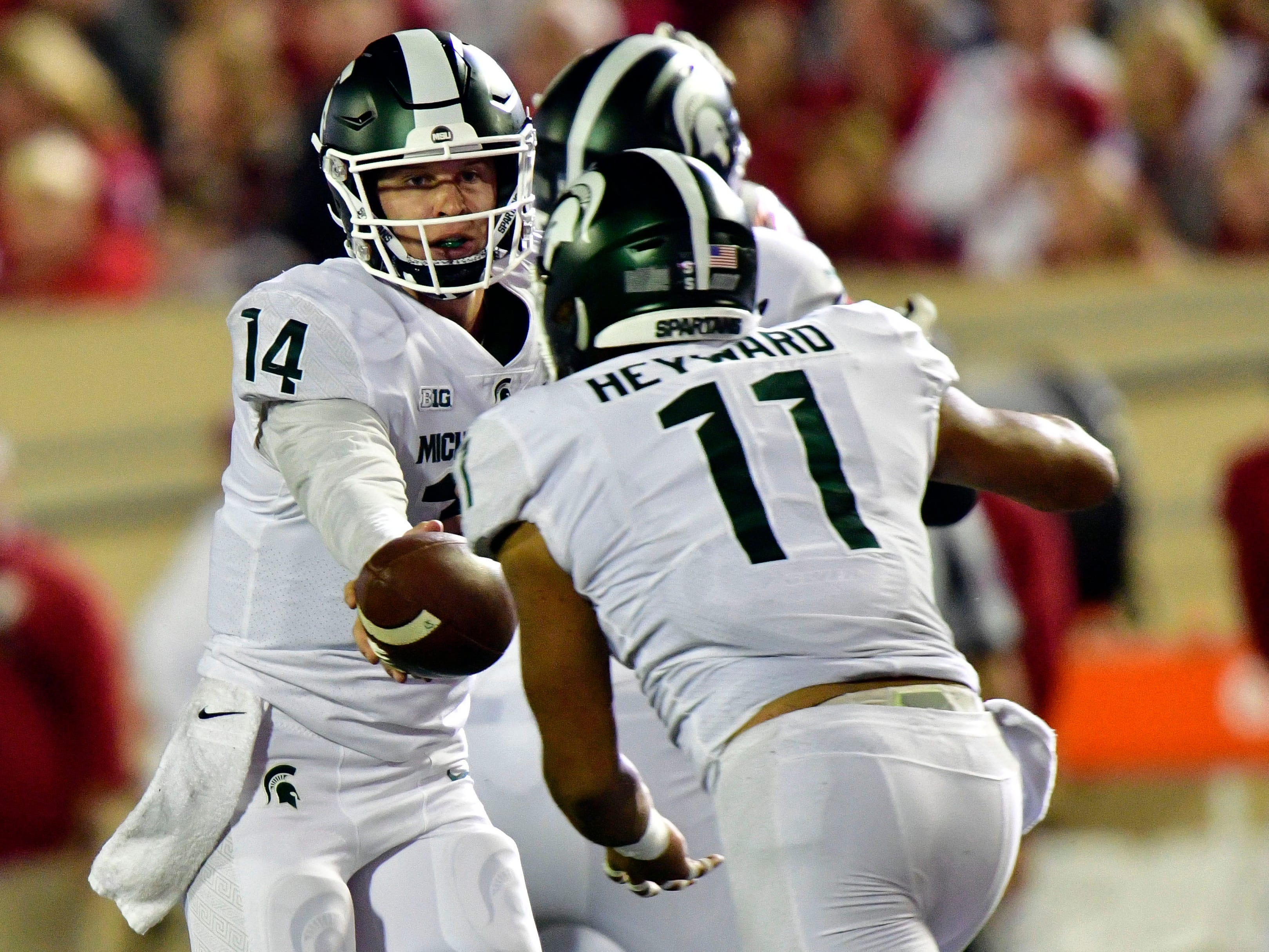 Michigan State Spartans quarterback Brian Lewerke (14) hands the ball off to running back Connor Heyward (11)  during the second quarter of the game at Memorial Stadium.
