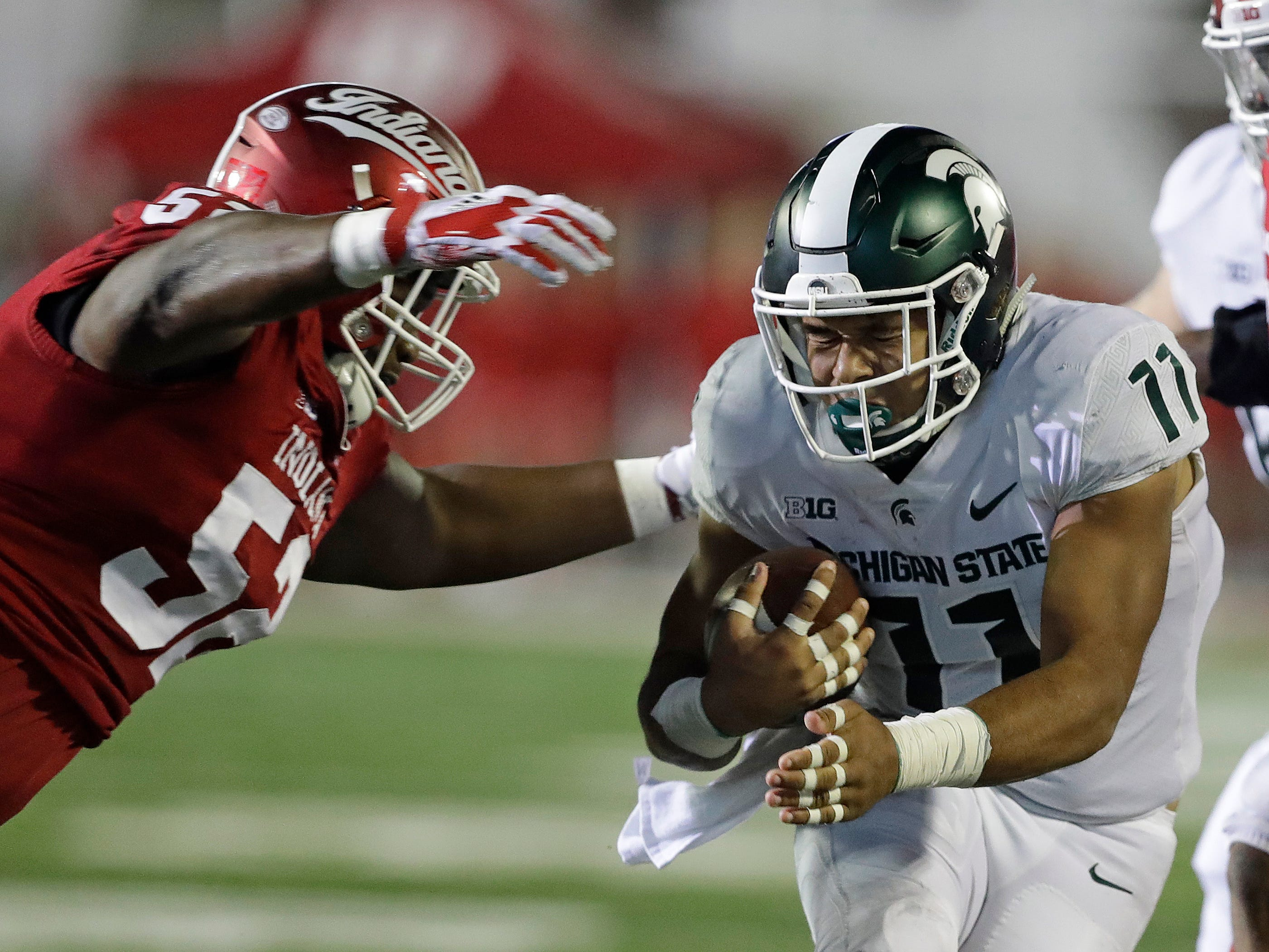 Michigan State running back Connor Heyward (11) is tackled by Indiana's Kayton Samuels during the second half of an NCAA college football game, Saturday, Sept. 22, 2018, in Bloomington, Ind. Michigan State won 35-21.