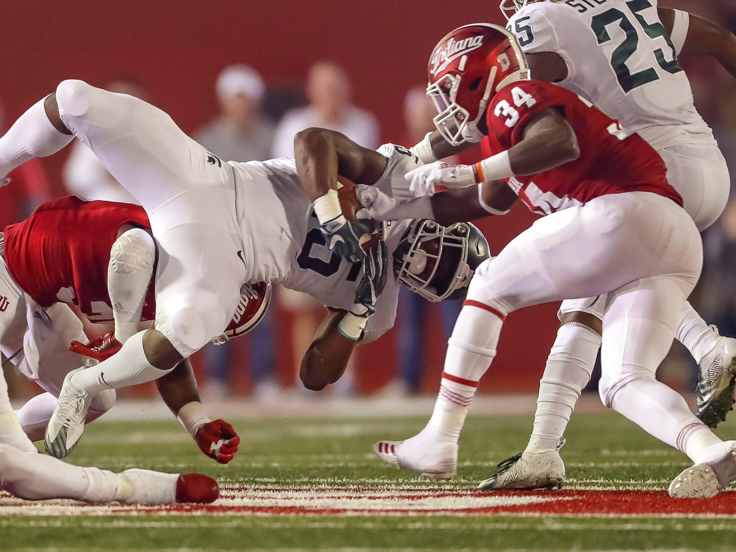 La'Darius Jefferson #15 of the Michigan State Spartans runs the ball as Cam Jones #34 of the Indiana Hoosiers punches the ball away causing a fumble during the first half of action at Memorial Stadium on September 22, 2018 in Bloomington, Indiana.