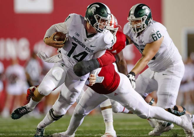Brian Lewerke #14 of the Michigan State Spartans is tackled for a sack by Nile Sykes #35 of the Indiana Hoosiers during the first half of action at Memorial Stadium on September 22, 2018 in Bloomington, Indiana.
