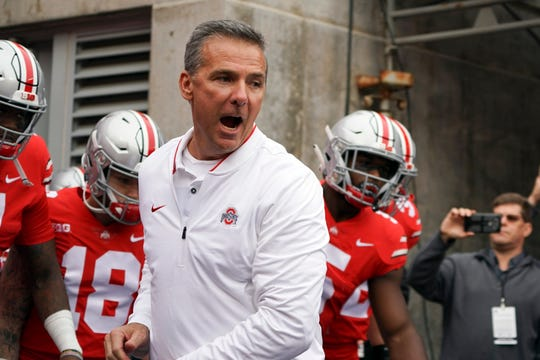 Ohio State coach Urban Meyer, on the sidelines for the first time since serving a three-game suspension, gets fired up as he prepares to lead the Buckeyes out of the tunnel for Saturday's game against Tulane.