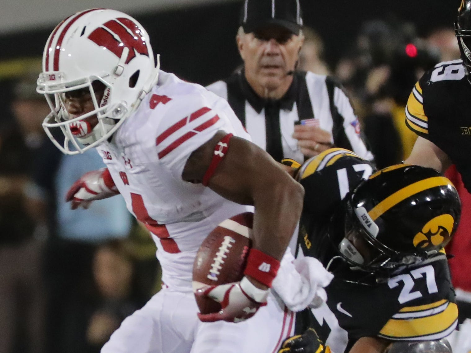 Wisconsin wide receiver A.J. Taylor   picks up 22 yards on a reception despite the efforts of Iowa defensive back Amani Hooker.