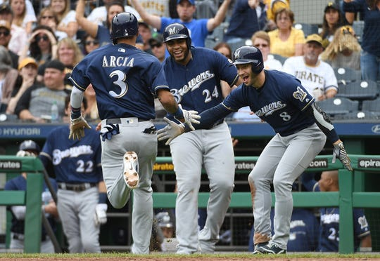 Orlando Arcia (3) of the Milwaukee Brewers is greeted at home plate by Ryan Braun (right) and Jesus Aguilar after coming around to score on a wild pitch and an error by Michael Feliz of the Pittsburgh Pirates in the sixth inning at PNC Park on September 23, 2018