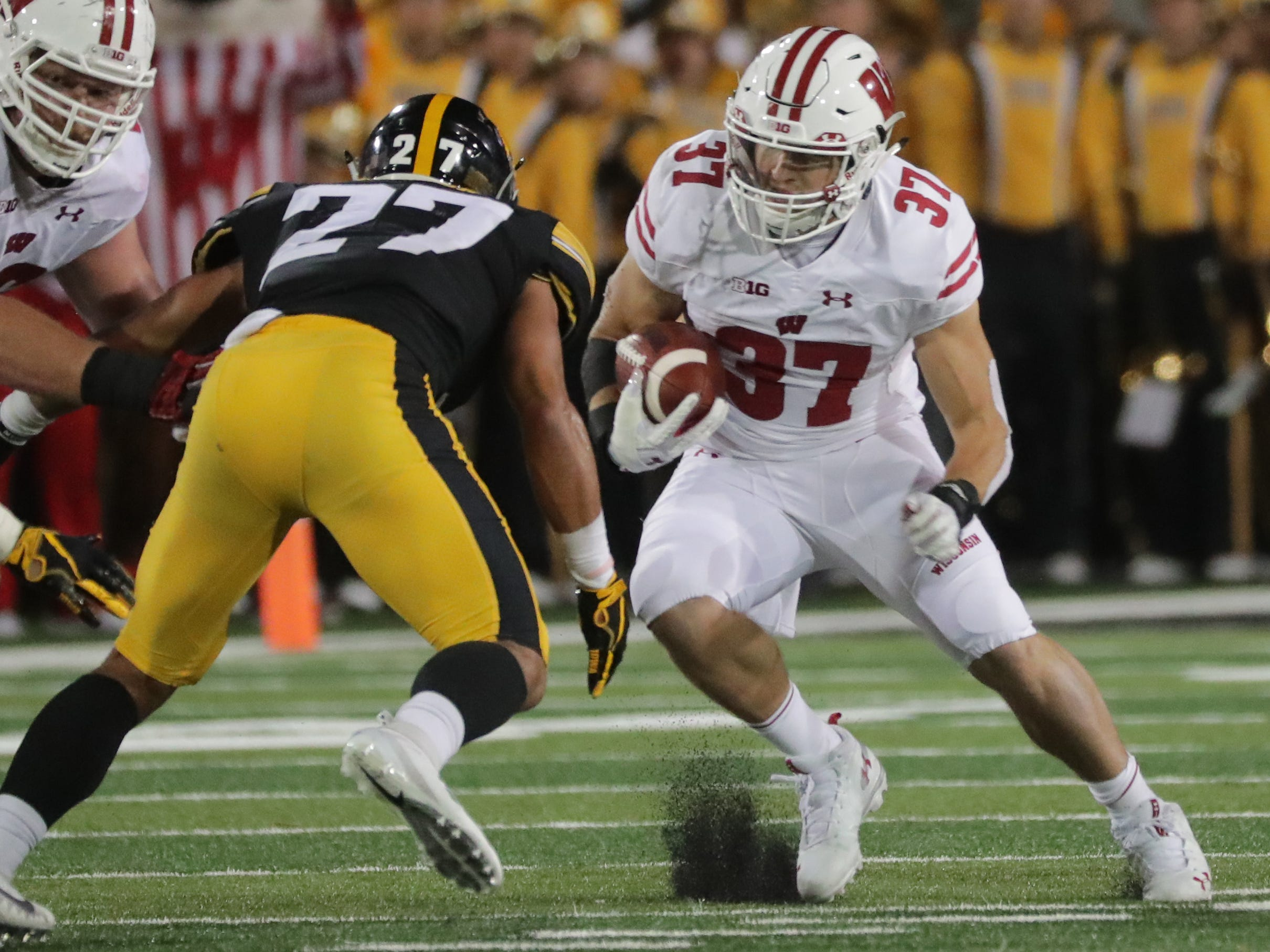 Wisconsin running back Garrett Groshek is stopped short of first down by Iowa defensive back Amani Hooker.