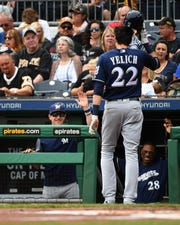 Christian Yelich reaches a happy Brewers dugout after he scored when Mike Moustakas was hit by a pitch from Pirates starter Nick Kingham with the bases loaded in the first inning Sunday.
