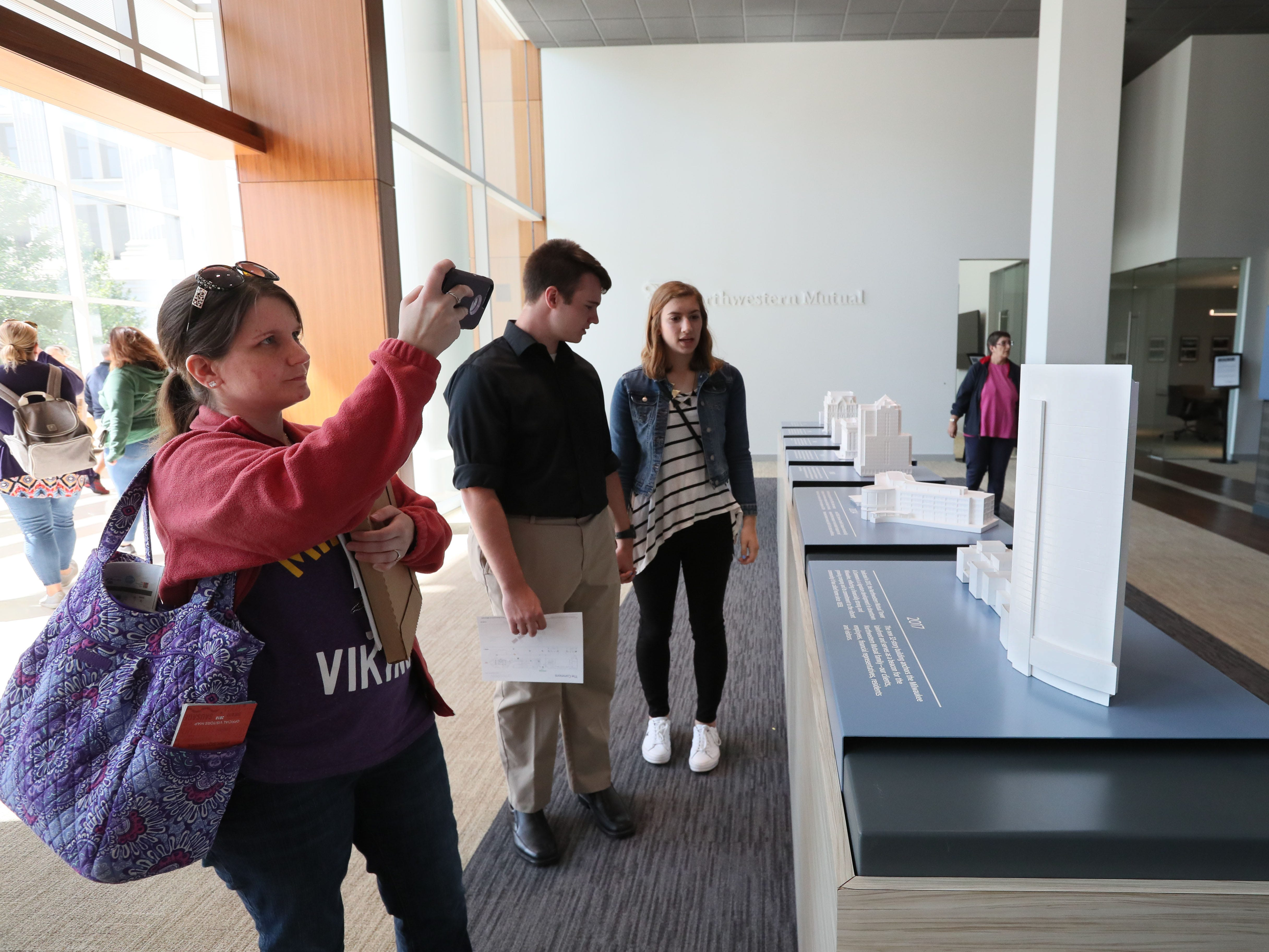 Kirstina Lemke of Appleton photographs models of  Northwestern Mutual Life Insurance Co. buildings throughout its history while Bryan Roob and Kelsey Koepke of Milwaukee read about the buildings while inside the Northwestern Mutual Tower and Commons on Sunday.