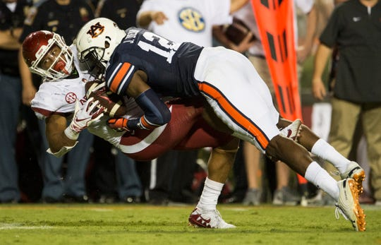 Auburn's Jamel Dean (12) blows up a screen pass tackling Arkansas' Devwah Whaley (21) in the backfield at Jordan-Hare Stadium in Auburn, Ala., on Saturday, Sept. 21, 2018. Auburn defeated Arkansas 34-3.