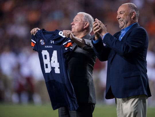 United States Attorney General Jeff Session holds up his honorary jersey with Auburn president Steven Leath during the Auburn vs. Arkansas game at Jordan-Hare Stadium in Auburn, Ala., on Saturday, Sept. 21, 2018. Auburn defeated Arkansas 34-3.