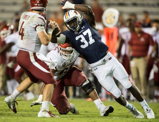 Auburn's Richard Jibunor (37) swats the ball out of Arkansas' Ty Storey (4) hand forcing a fumble at Jordan-Hare Stadium in Auburn, Ala., on Saturday, Sept. 21, 2018. Auburn defeated Arkansas 34-3.