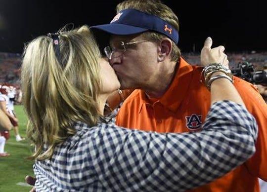 Auburn head coach Gus Malzahn kisses his wife Kristi, after a victory over Arkansas Saturday, Sept. 22, 2018, at Jordan-Hare Stadium in Auburn, Ala.