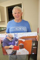 Selma dentist Donald Russell holds an enlarged photo of him examining a young patient in Kenya.