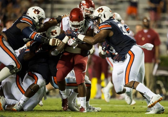 Arkansas' Maleek Williams (23) is taken down by a swarm of Auburn defenders at Jordan-Hare Stadium in Auburn, Ala., on Saturday, Sept. 21, 2018. Auburn defeated Arkansas 34-3.