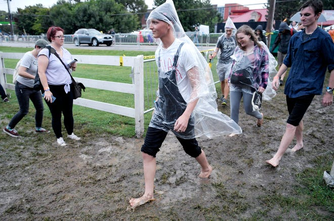 Music fans walk through the mud after storms delayed Pilgrimage Music & Cultural Festival on Saturday, Sept. 22, 2018.