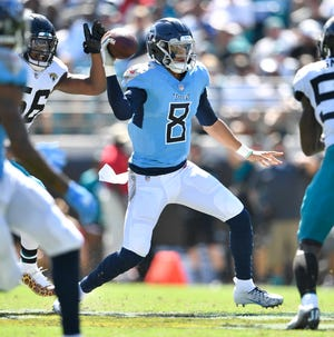 Titans quarterback Marcus Mariota (8) scrambles out of the pocket short of the first down against the Jaguars on Sunday.