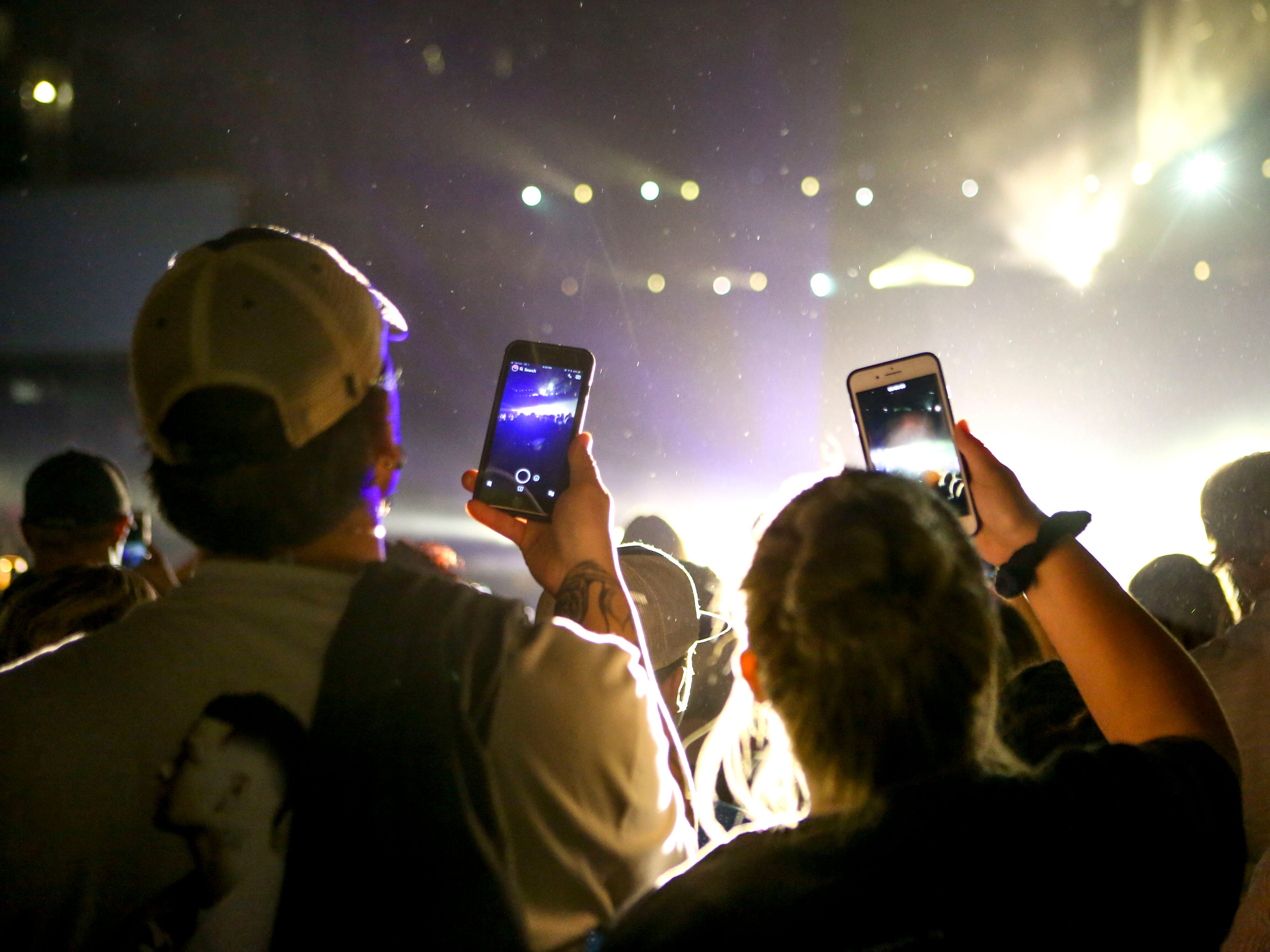 Fans wearing Kane Brown t-shirts take video and photo with their phones while Kane Brown performs as an opening act for Chris Young at Bridgestone Arena in Nashville, Tenn., Saturday, Sept. 22, 2018.