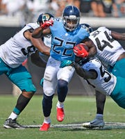 Titans running back Derrick Henry (22) powers through the Jaguars defense in the fourth quarter.