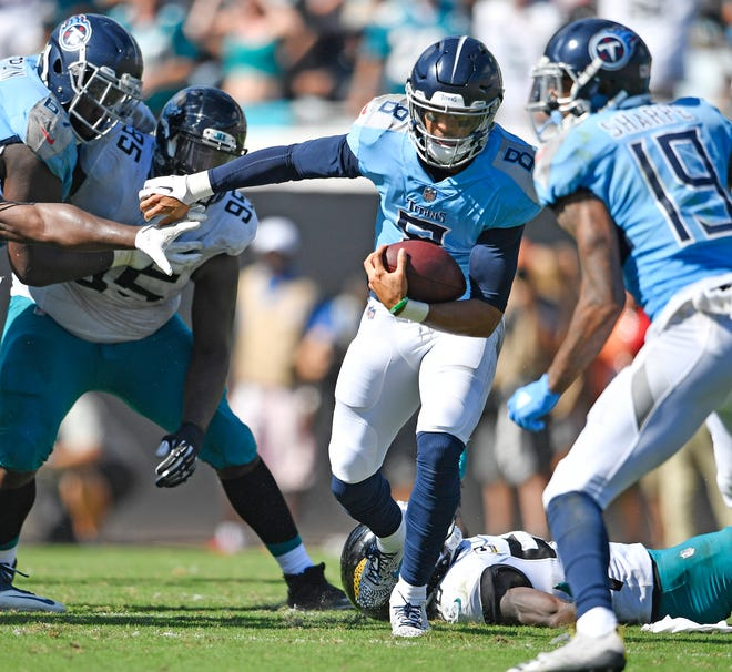 Titans quarterback Marcus Mariota (8) rushes for a first down in the first quarter Sunday.