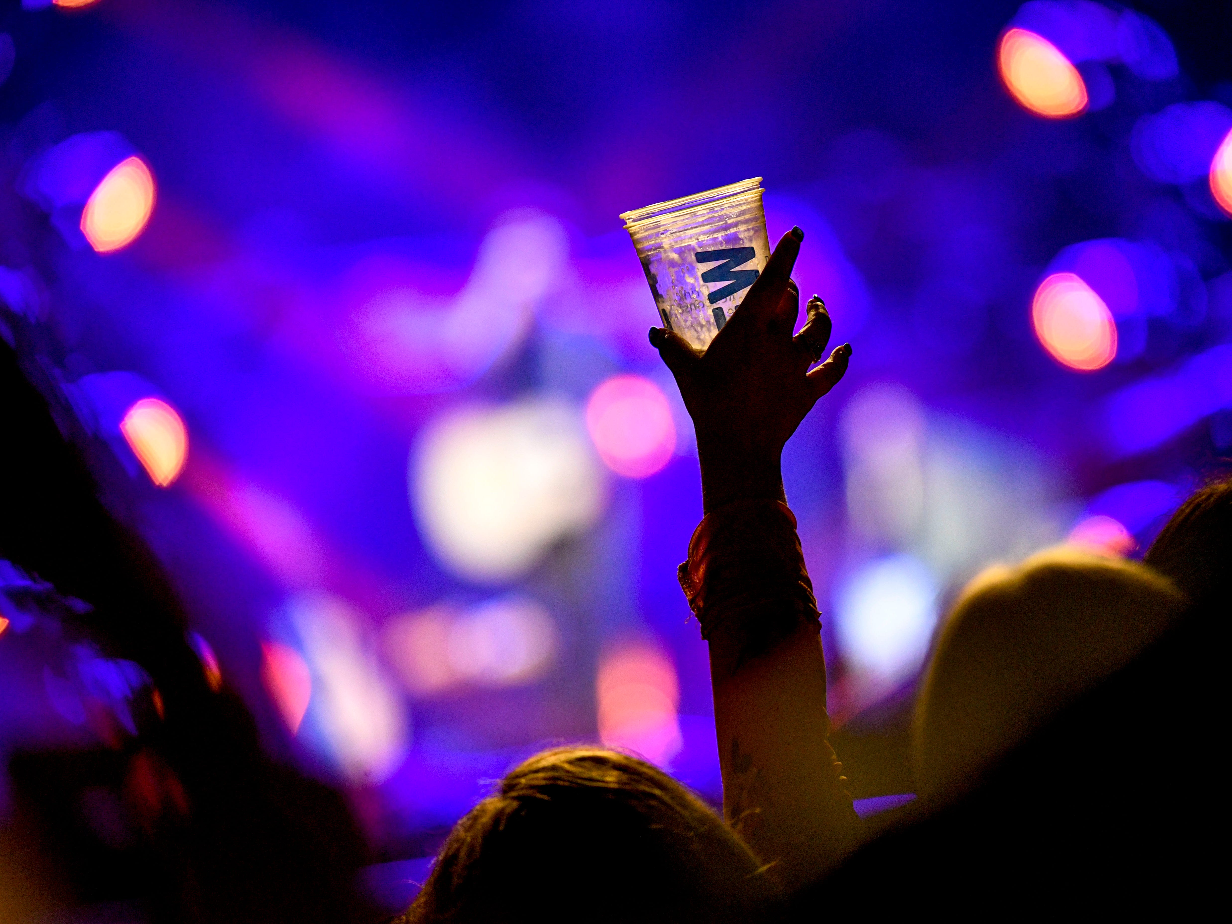 A fan raises a glass in the air while Morgan Evans performs as an opening act for Chris Young at Bridgestone Arena in Nashville, Tenn., Saturday, Sept. 22, 2018.