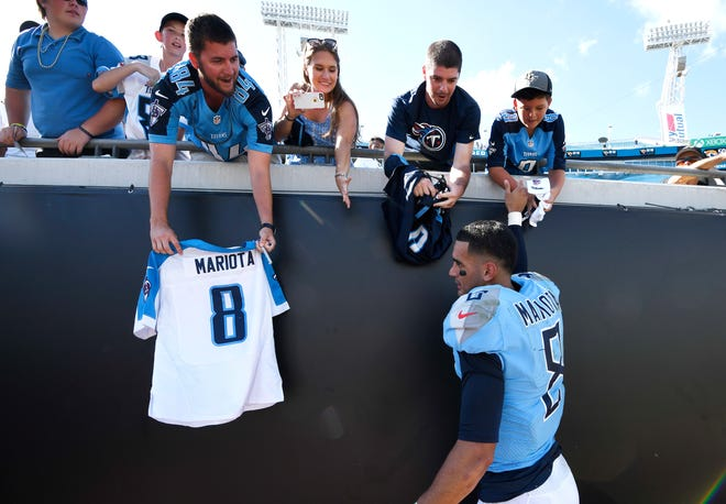 Titans quarterback Marcus Mariota (8) signs autographs for fans after the team's 9-6 win over the Jaguars on Sunday.