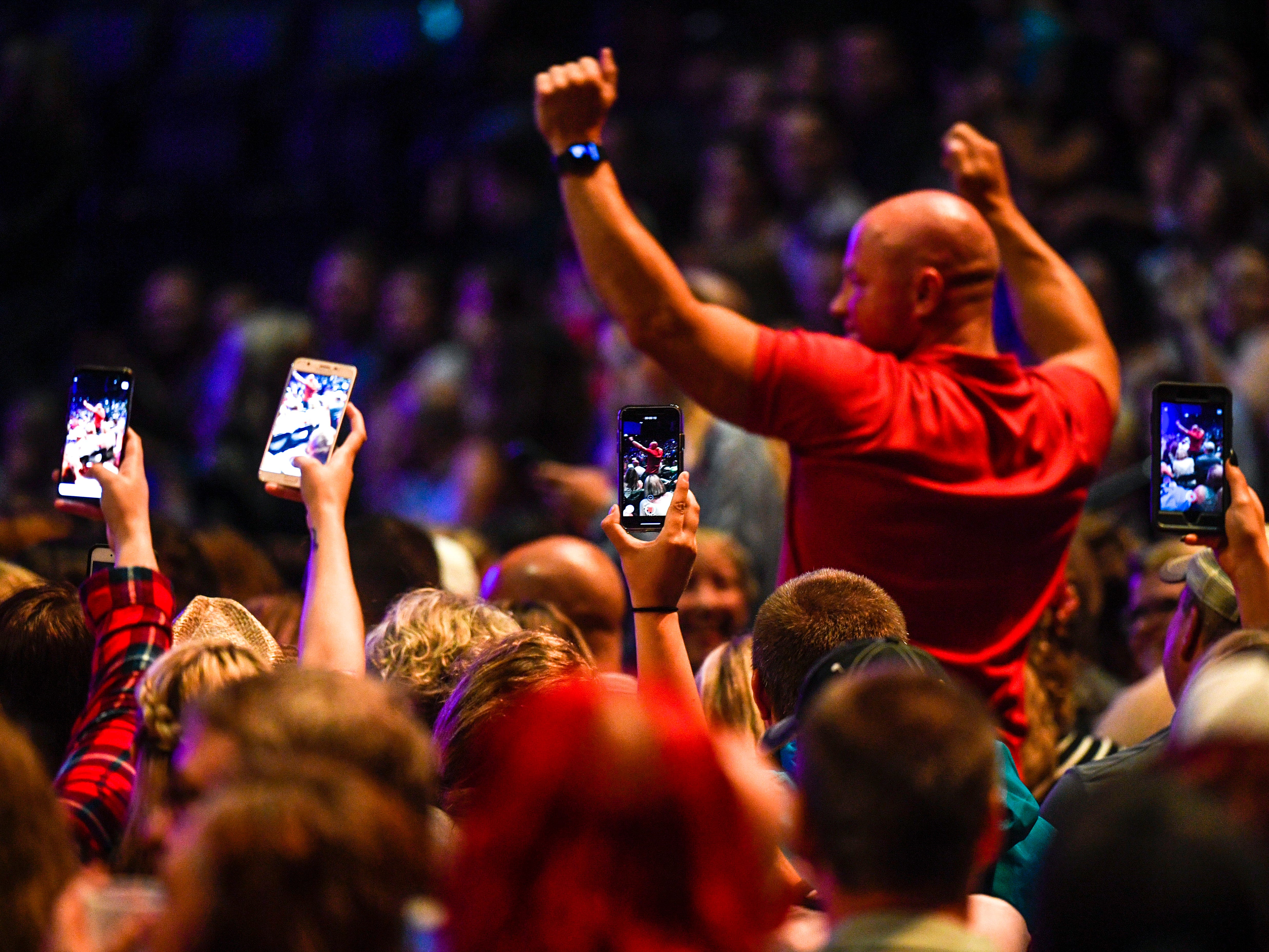 Spectators take video of a man dancing to music played in between sets before Kane Brown performs as an opening act for Chris Young at Bridgestone Arena in Nashville, Tenn., Saturday, Sept. 22, 2018.