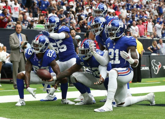 Sep 23, 2018; Houston, TX, USA; New York Giants linebacker Alec Ogletree (52) celebrates with teammates by striking a pose after his interception in the end zone during the fourth quarter against the Houston Texans at NRG Stadium.