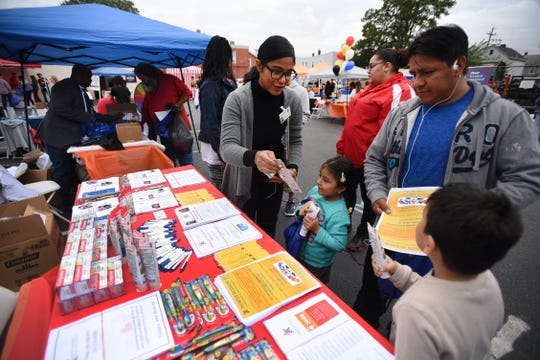 Leslie Ynoa of North Hudson Community Action Corp., gives a   toothbrush to Ashelly (age 5) as her father Luis Pacheco of Hackensack and his son Joy (age 5) look on during the first annual Resource and Community Wellness Fair held by Buddies of NJ in Hackensack on 0923/18. The Buddies support people living with or affected by HIV/AIDS