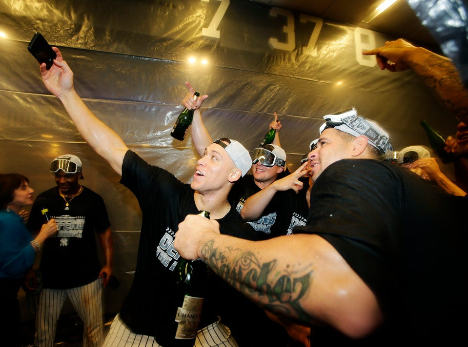 New York Yankees' Aaron Judge, left, celebrates with teammates after they clinched wildcard playoff birth with a 3-2 win over the Baltimore Orioles in a baseball game Saturday, Sept. 22, 2018, in New York.