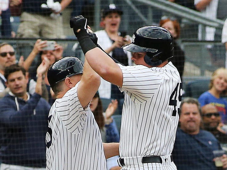 Yankees first baseman Luke Voit (45) is congratulated by third base coach Phil Nevin (35) after hitting a solo home run against the Baltimore Orioles during the second inning at Yankee Stadium.