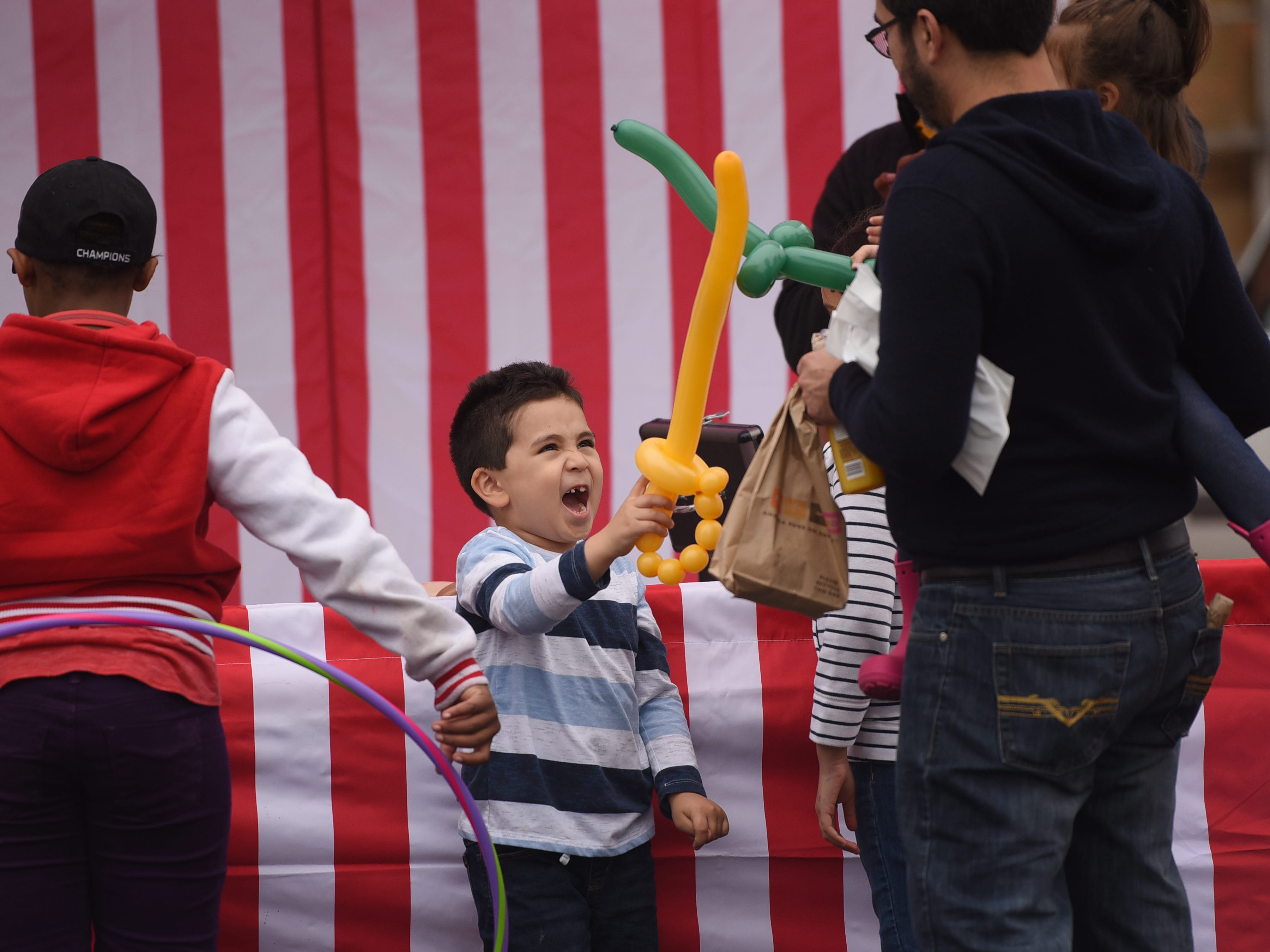 Hector Torres (age 5) of Hackensack shows his balloon sword to his father Jose (standing R) during the first annual Resource and Community Wellness Fair held by Buddies of NJ in Hackensack on 0923/18. The Buddies support people living with or affected by HIV/AIDS