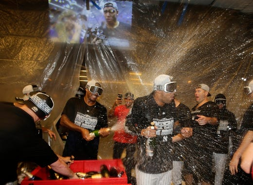 The New York Yankees celebrate after they clinched wildcard playoff birth with a 3-2 win over the Baltimore Orioles in a baseball game Saturday, Sept. 22, 2018, in New York.