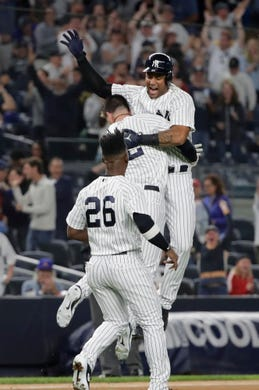 New York Yankees' Aaron Hicks celebrates with teammates after hitting a RBI double during the eleventh inning of a baseball game against the Baltimore Orioles Saturday, Sept. 22, 2018, in New York.