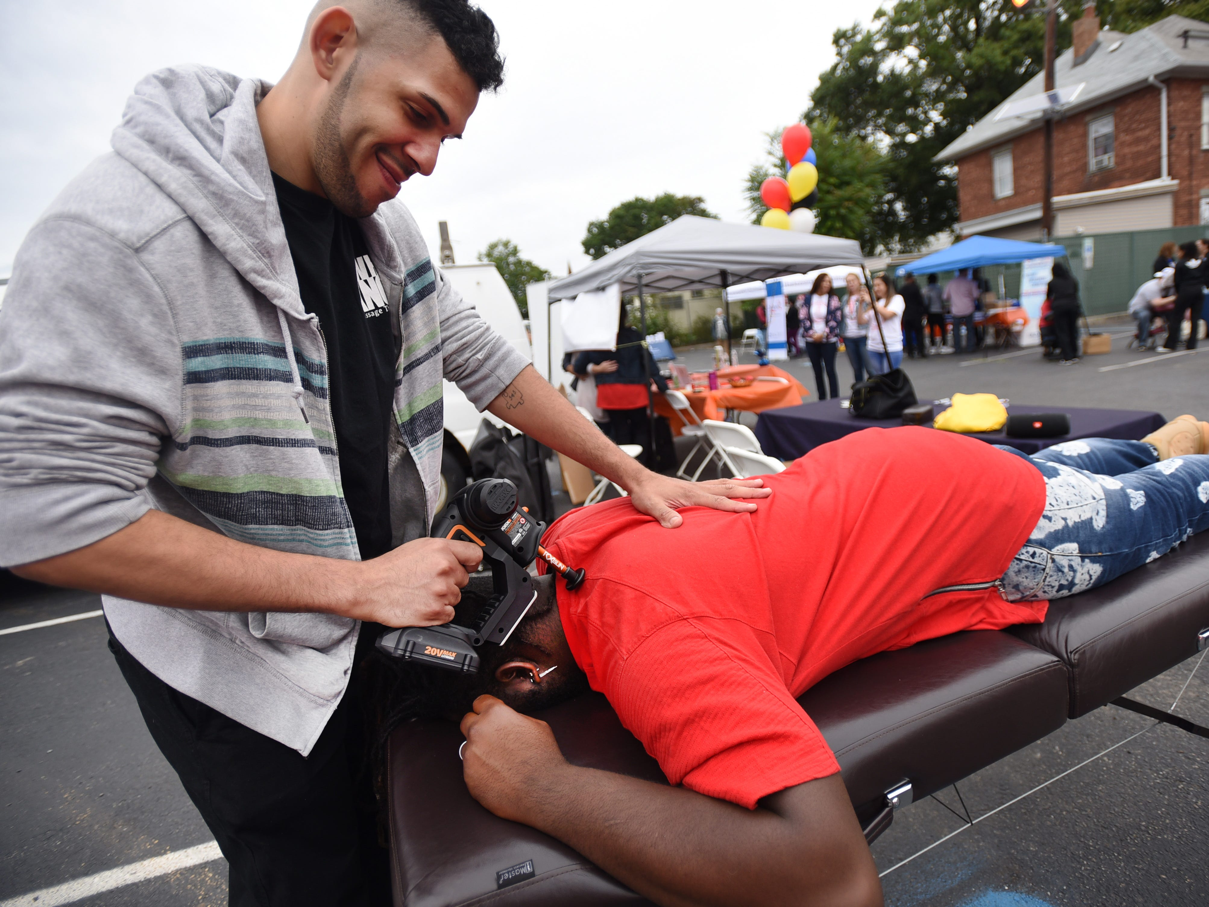 Luis Ramos of Why Knot You Massage Therapy, gives a massage by RX gun, which is used for sports medicine massage, during the first annual Resource and Community Wellness Fair held by Buddies of NJ in Hackensack on 0923/18. The Buddies support people living with or affected by HIV/AIDS