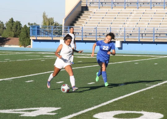 Nyah Chacon chases down a Lady Warriors player during Saturday's game against Santa Teresa at Caveman Stadium. Chacon finished the game with two goals.