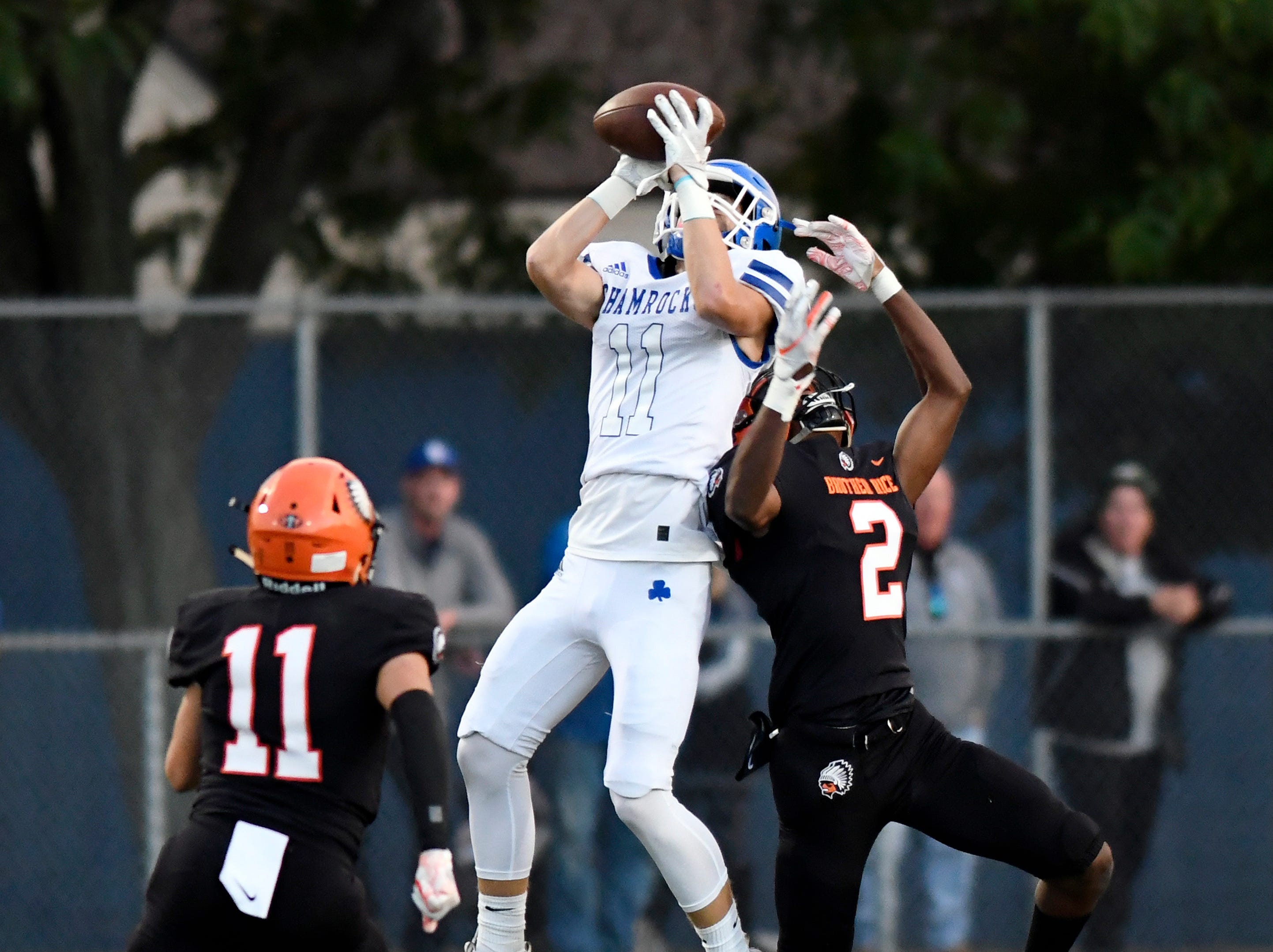 Detroit Catholic Central wide receiver Nate Anderson (11), middle, hauls in a pass in between Birmingham Brother Rice safety Giavino Murad (11), left, and cornerback Jonathon Tillman (2) in the second quarter, Saturday, Sept. 22, 2018 at Hurley Field in Berkley, Mich.  Catholic Central defeated Brother Rice, 21-0.