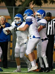 Detroit Catholic Central wide receiver Ryan Birney (14), far left, is congratulated by teammates after scoring a touchdown against Birmingham Brother Rice in the second quarter, Saturday, Sept. 22, 2018 at Hurley Field in Berkley, Mich.  Catholic Central defeated Brother Rice, 21-0.  (Jose Juarez/Hometown Life)
