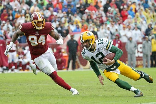 Sep 23, 2018; Landover, MD, USA; Green Bay Packers quarterback Aaron Rodgers (12) runs with the ball as Washington Redskins linebacker Preston Smith (94) chases in the second quarter at FedEx Field. The Redskins won 31-17. Mandatory Credit: Geoff Burke-USA TODAY Sports