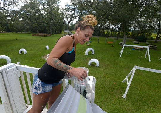 Terra Williams helps paint some of the attractions at Sonshine Family farms corn maze Sunday, September 23, 2018.