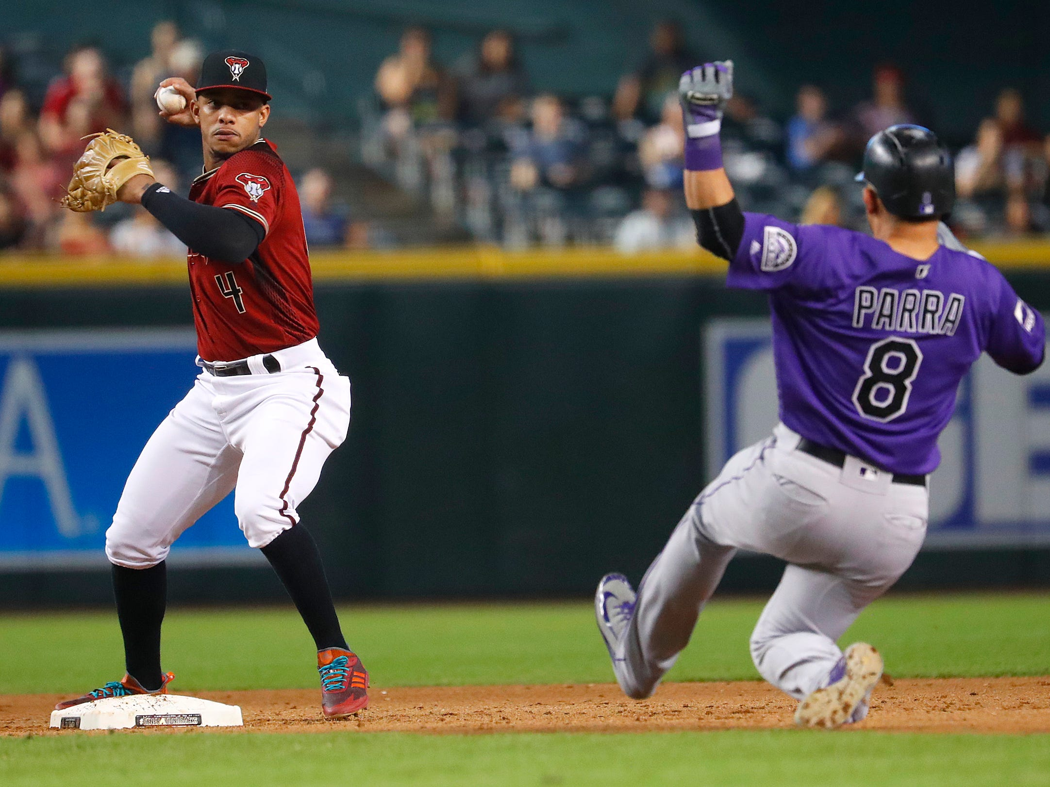 Diamondbacks Ketel Marte (4) records an out at second base on Rockies Gerardo Parra (8) and throws to to first for a double play during the fifth inning at Chase Field on Sept. 23, 2018.