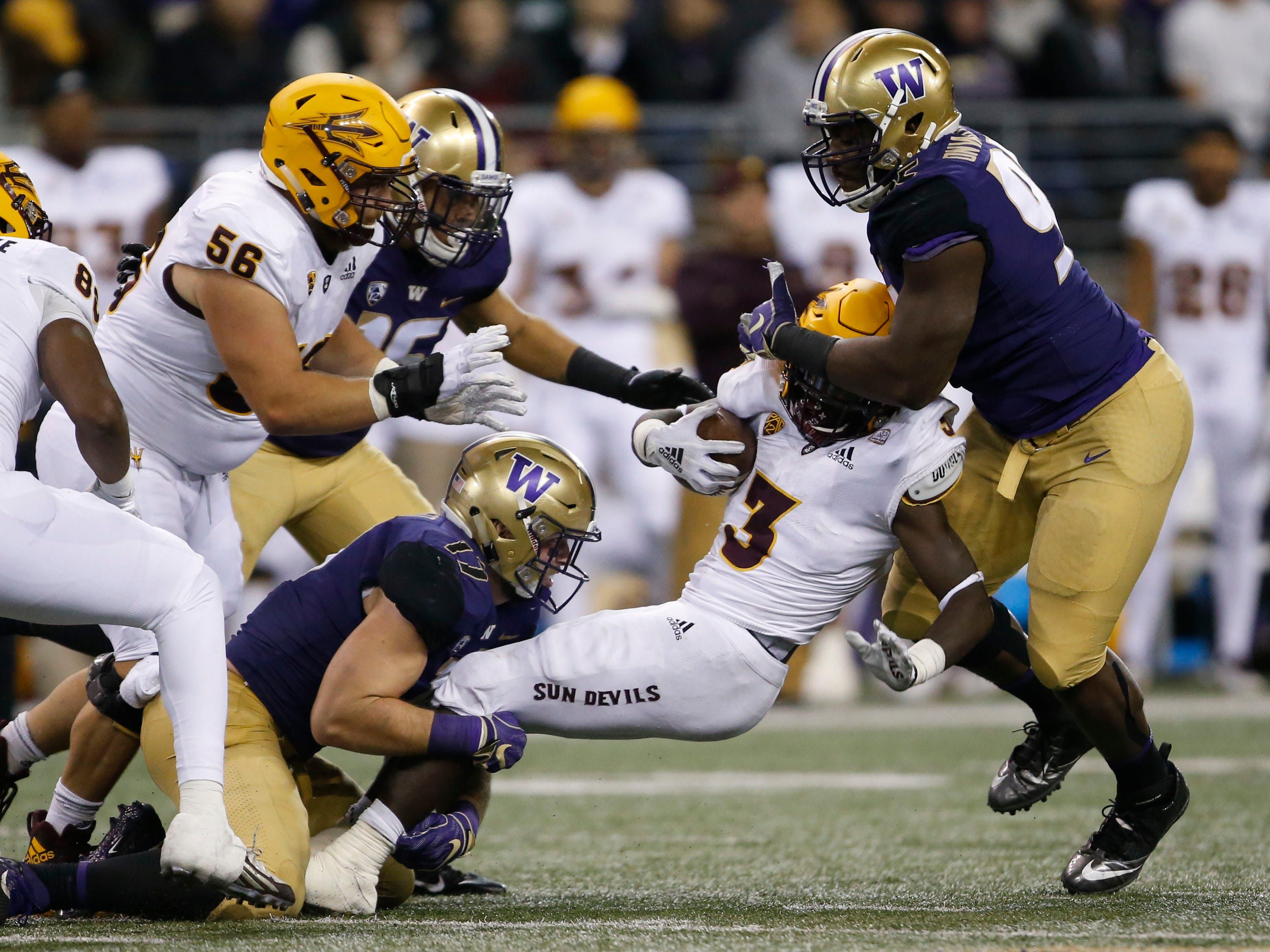 Sep 22, 2018; Seattle, WA, USA; Arizona State Sun Devils running back Eno Benjamin (3) gets tackled by Washington Huskies linebacker Tevis Bartlett (17) and defensive lineman Levi Onwuzurike (95) during the third quarter at Husky Stadium.