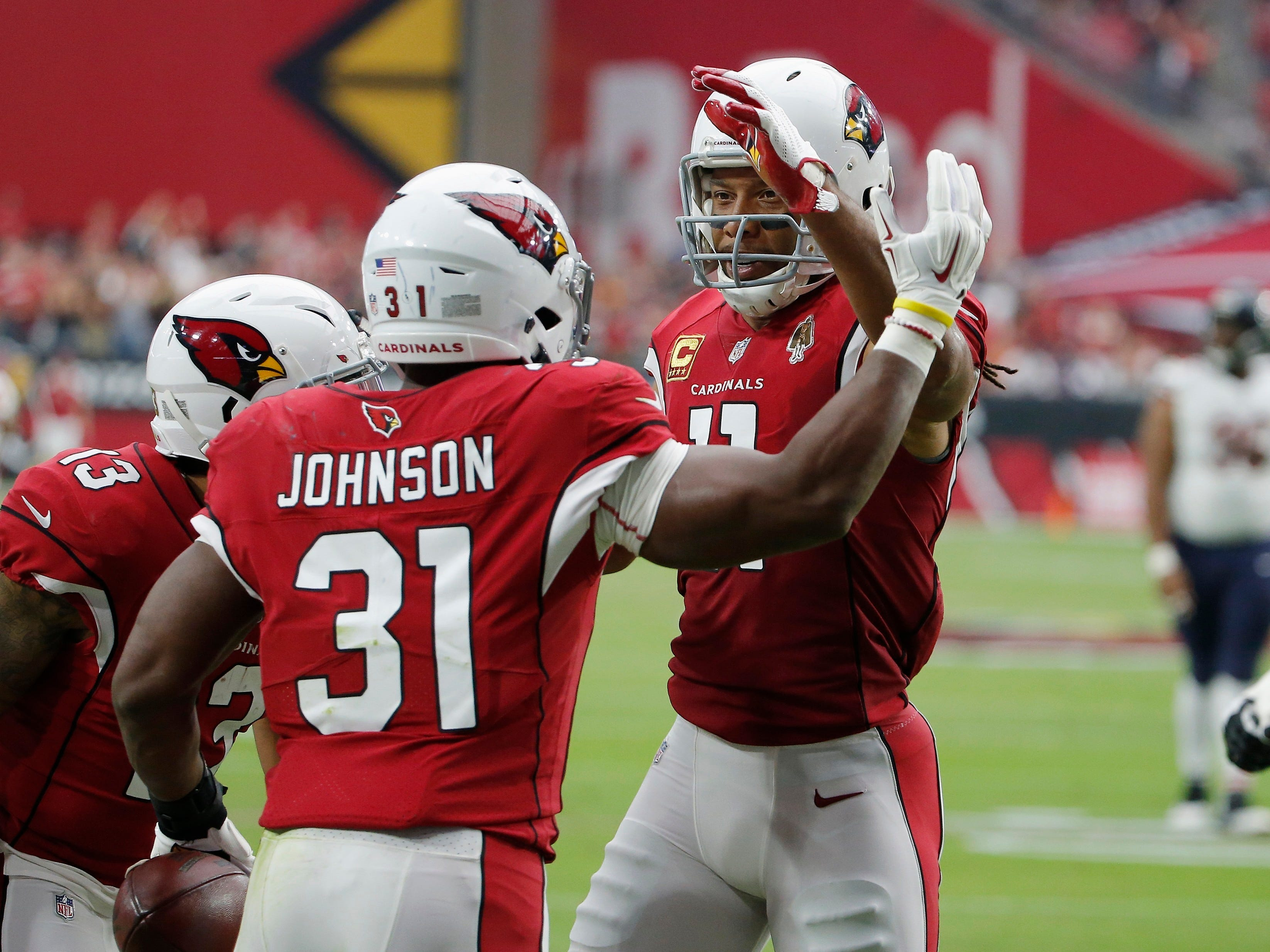 Arizona Cardinals running back David Johnson (31) celebrates his touchdown catch against the Chicago Bears with Larry Fitzgerald, right, and Christian Kirk (13) during the first half of an NFL football game, Sunday, Sept. 23, 2018, in Glendale, Ariz. (AP Photo/Rick Scuteri)