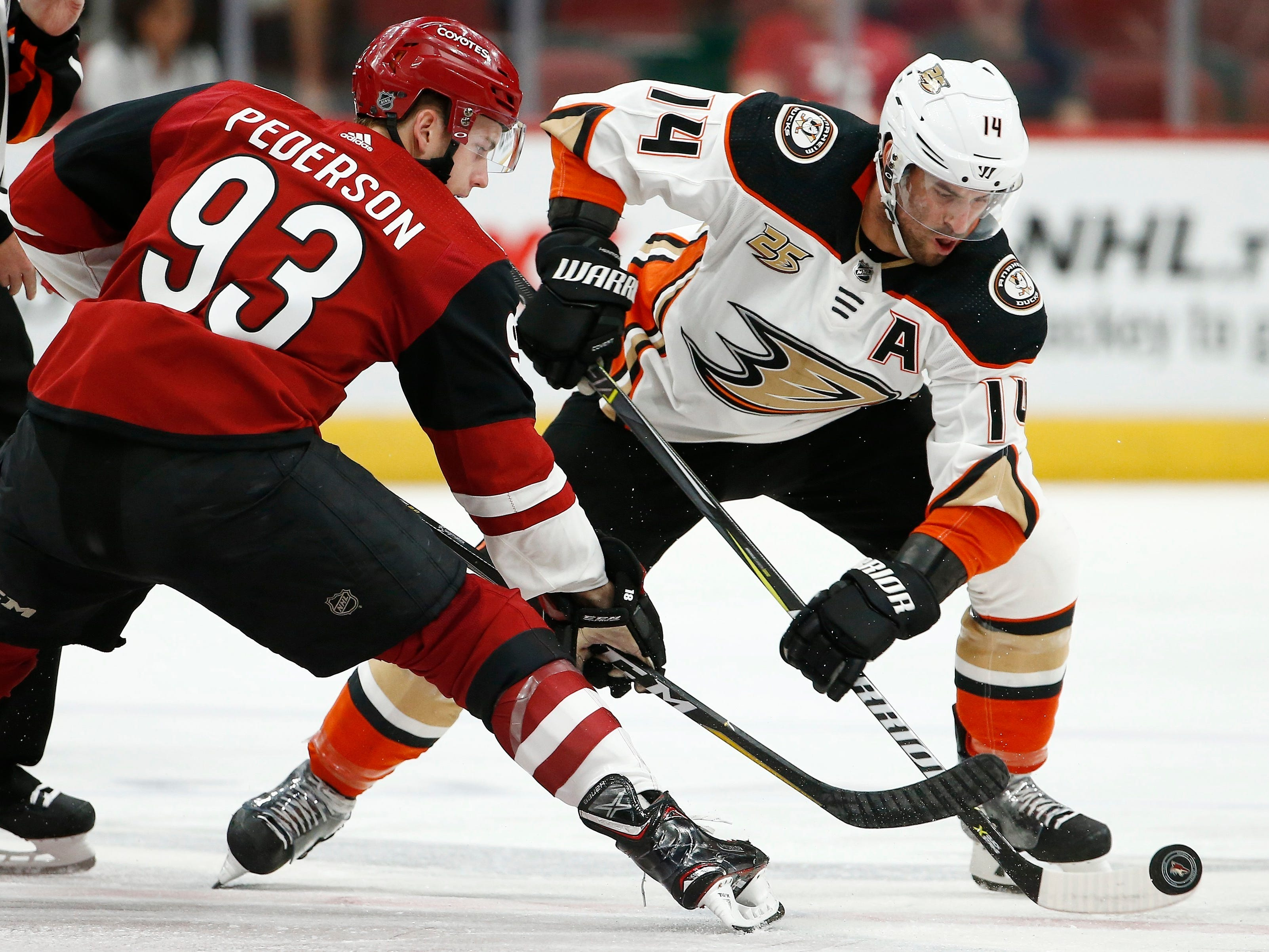 Anaheim Ducks center Adam Henrique (14) beats Arizona Coyotes center Lane Pederson (93) to the puck during the first period of an NHL preseason hockey game Saturday, Sept. 22, 2018, in Glendale, Ariz.